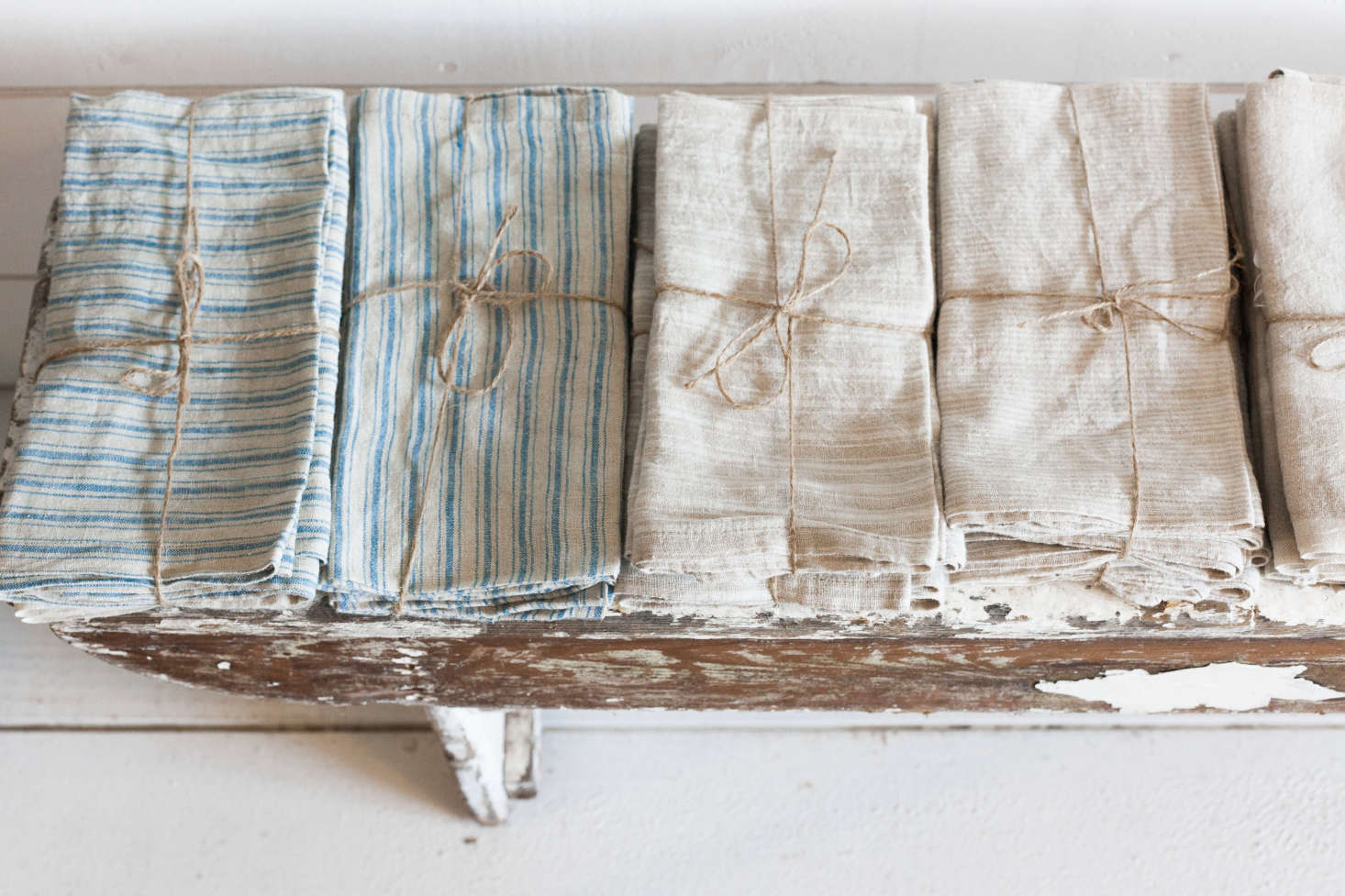 Table linens by Couleur Nature are tied with twine on an antique bench.