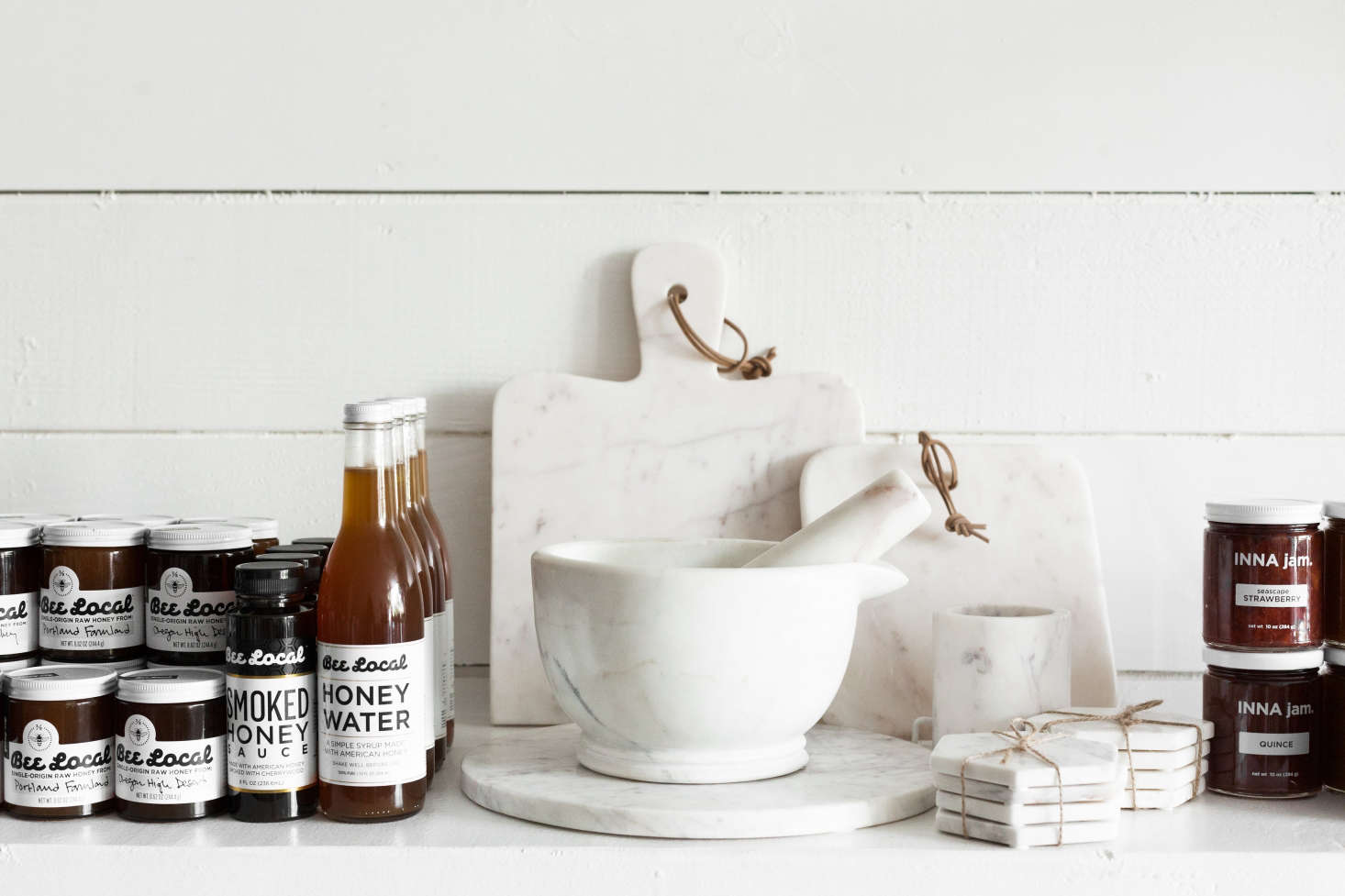 Flanking a trio of Couleur Nature marble serving boards: gifts from Bee Local in Portland, Oregon, and Inna Jam in Emeryville, California. The mortar and pestle is bySir/Madam.