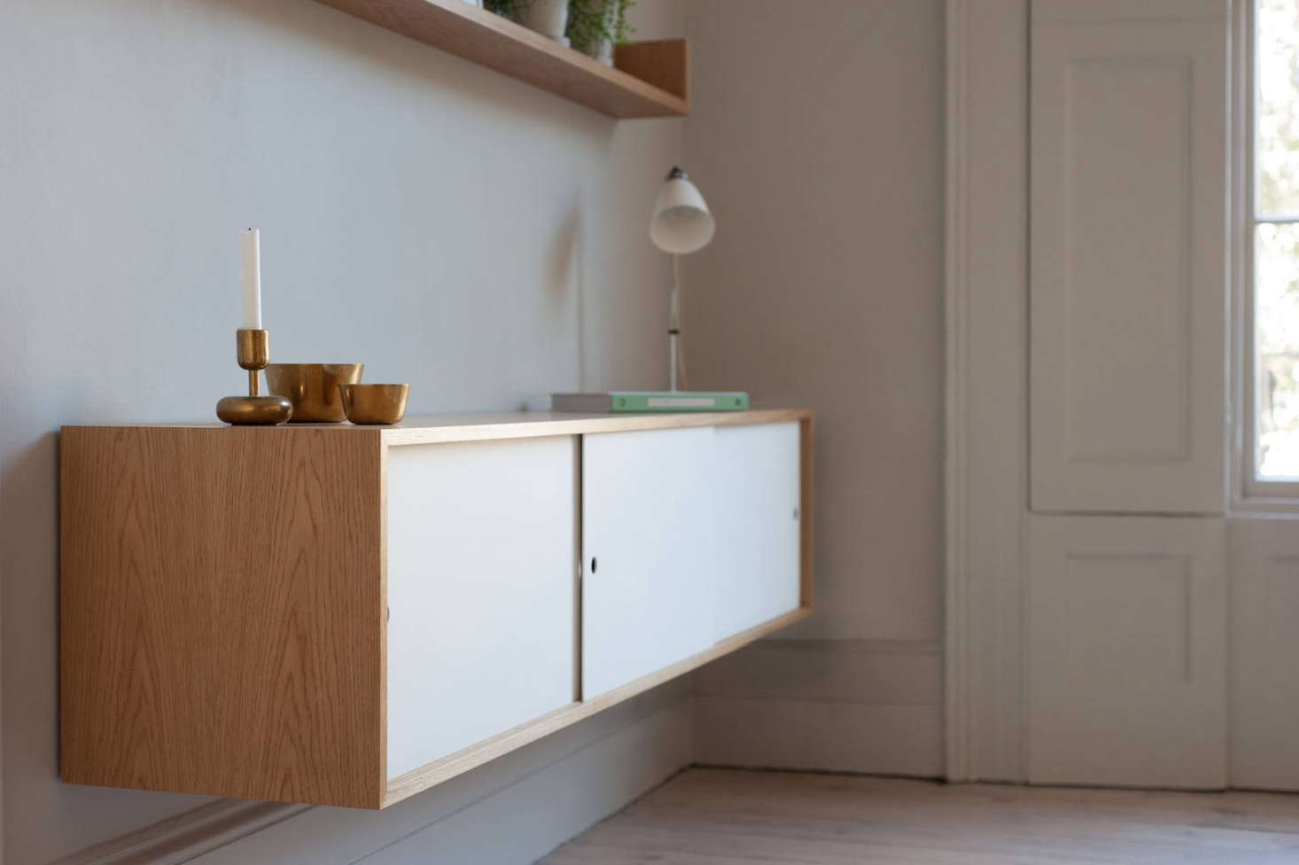 Next to the dining table is a Cantilevered Sideboard from Jack Trench, made of matching white oak with Corian sliding doors.