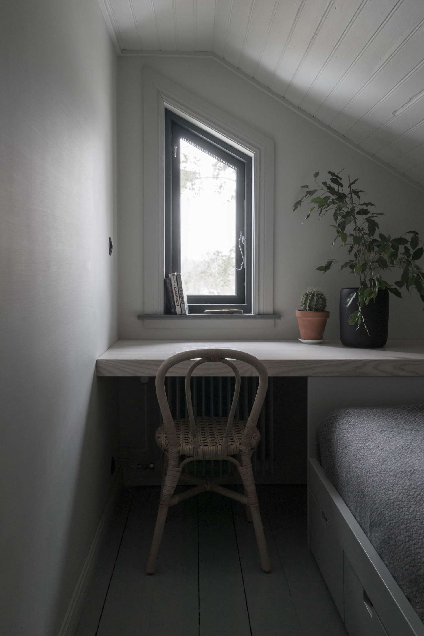 In a tiny bedroom, the architects maximized the space by installing a built-in bed with drawers and inserting a simple desk under a sliver of a window.