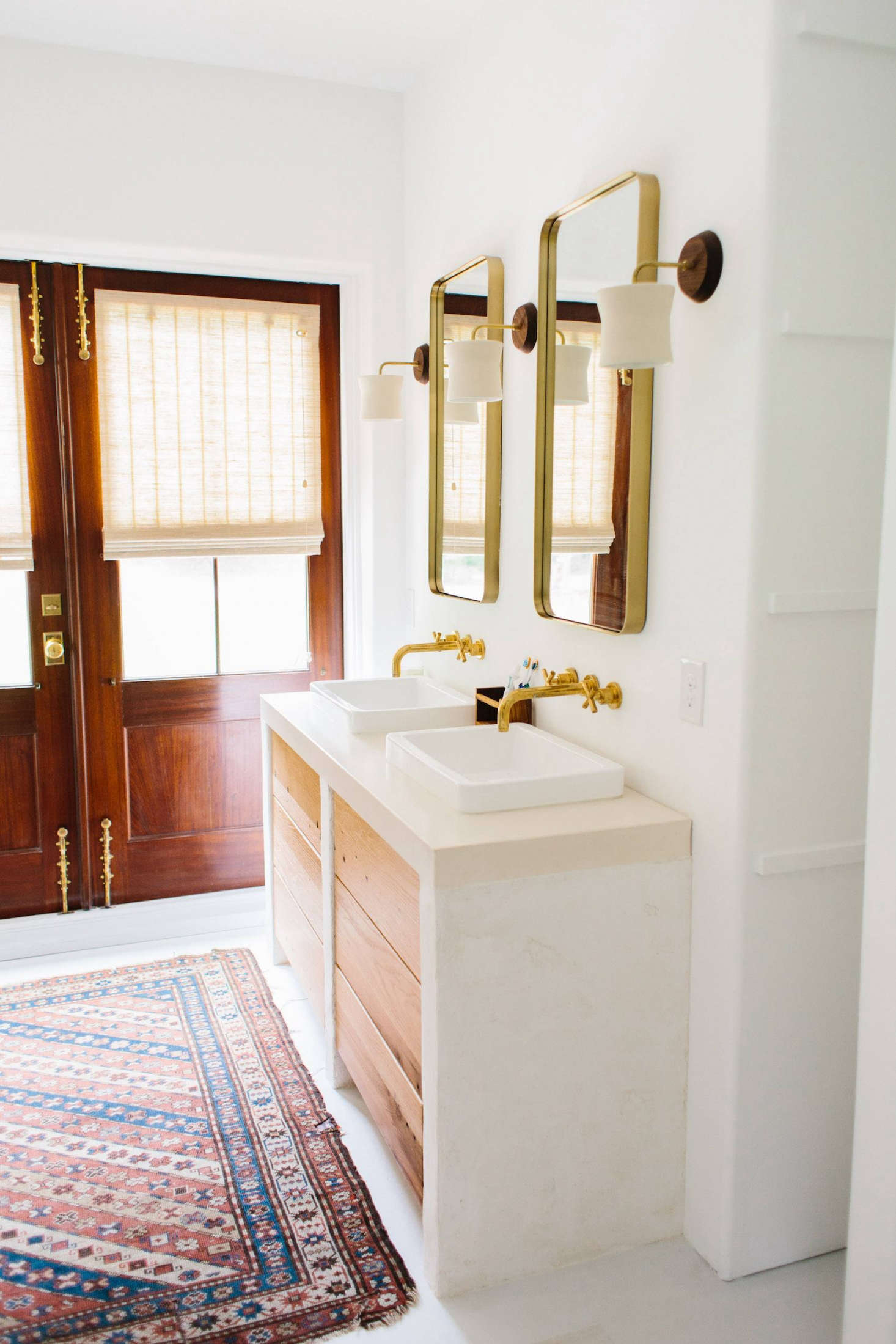 The master bathroom has a kilim rug and brass details. A pair of French doors opens onto the garden.