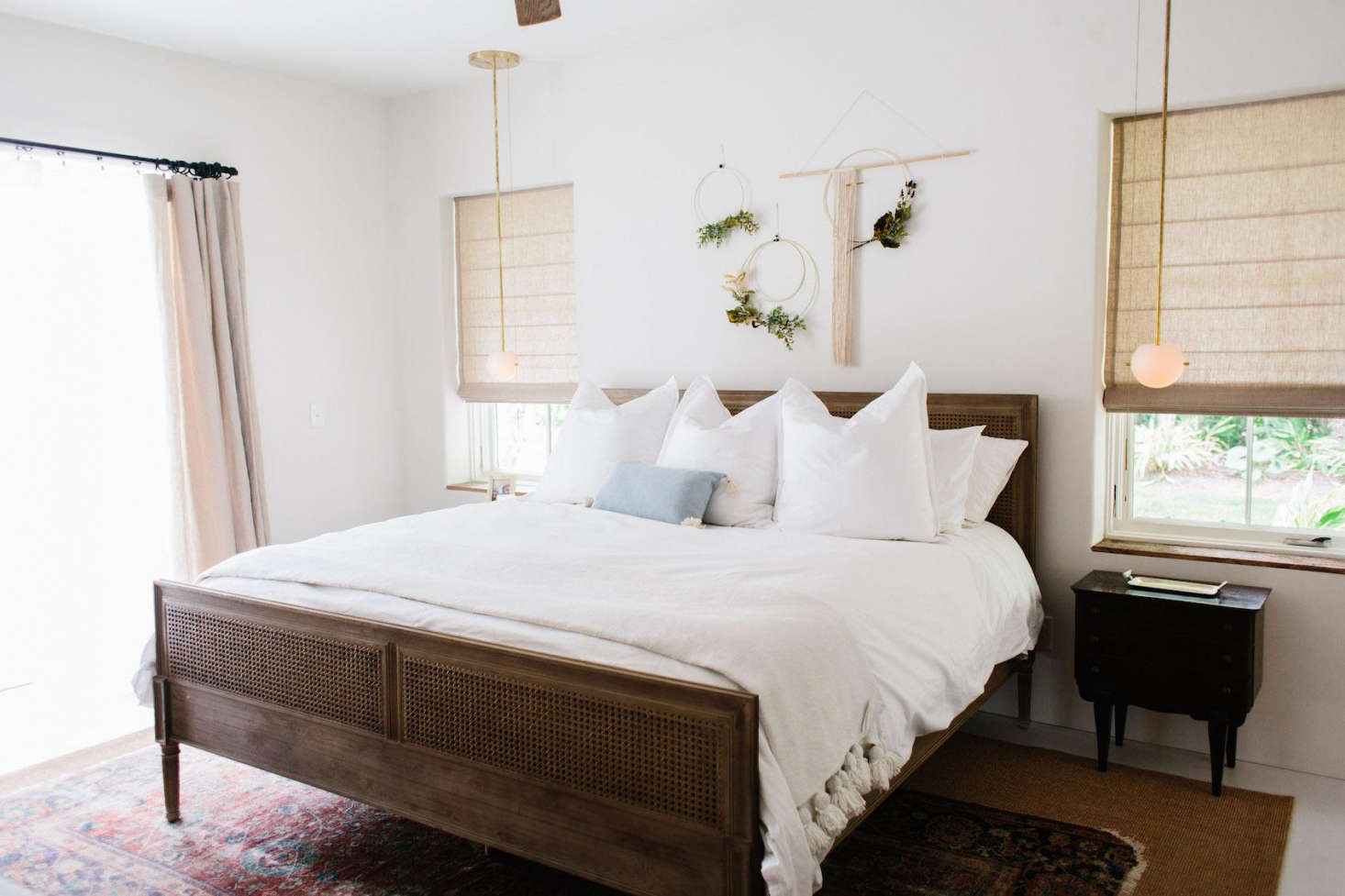 The master bedroom sports a Harbour Cane Bed from Serena & Lily. Flanking the bed are two Signal Pendants from Workstead. The flooring in all three bedrooms iswhite oak planks.