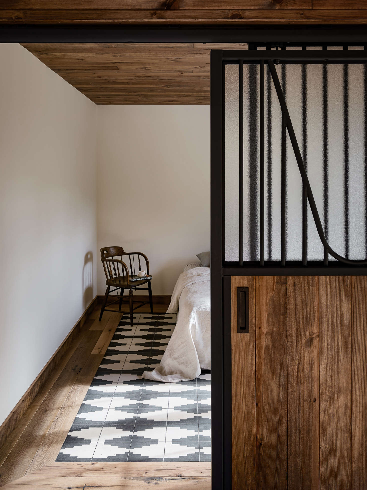 Though the guesthouse was rebuilt, the two bedrooms have the exact same dimensions and location as two preexisting horse-birthing stalls. Zames even used the same sliding doors, with refinished metal and obscured glass added for privacy.