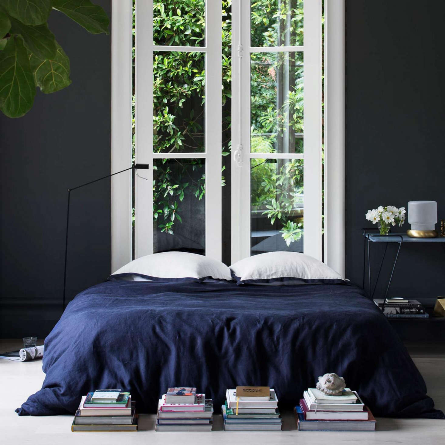Unique French doors and greenery in a navy bedroom with bedding from Cultiver of Australia a