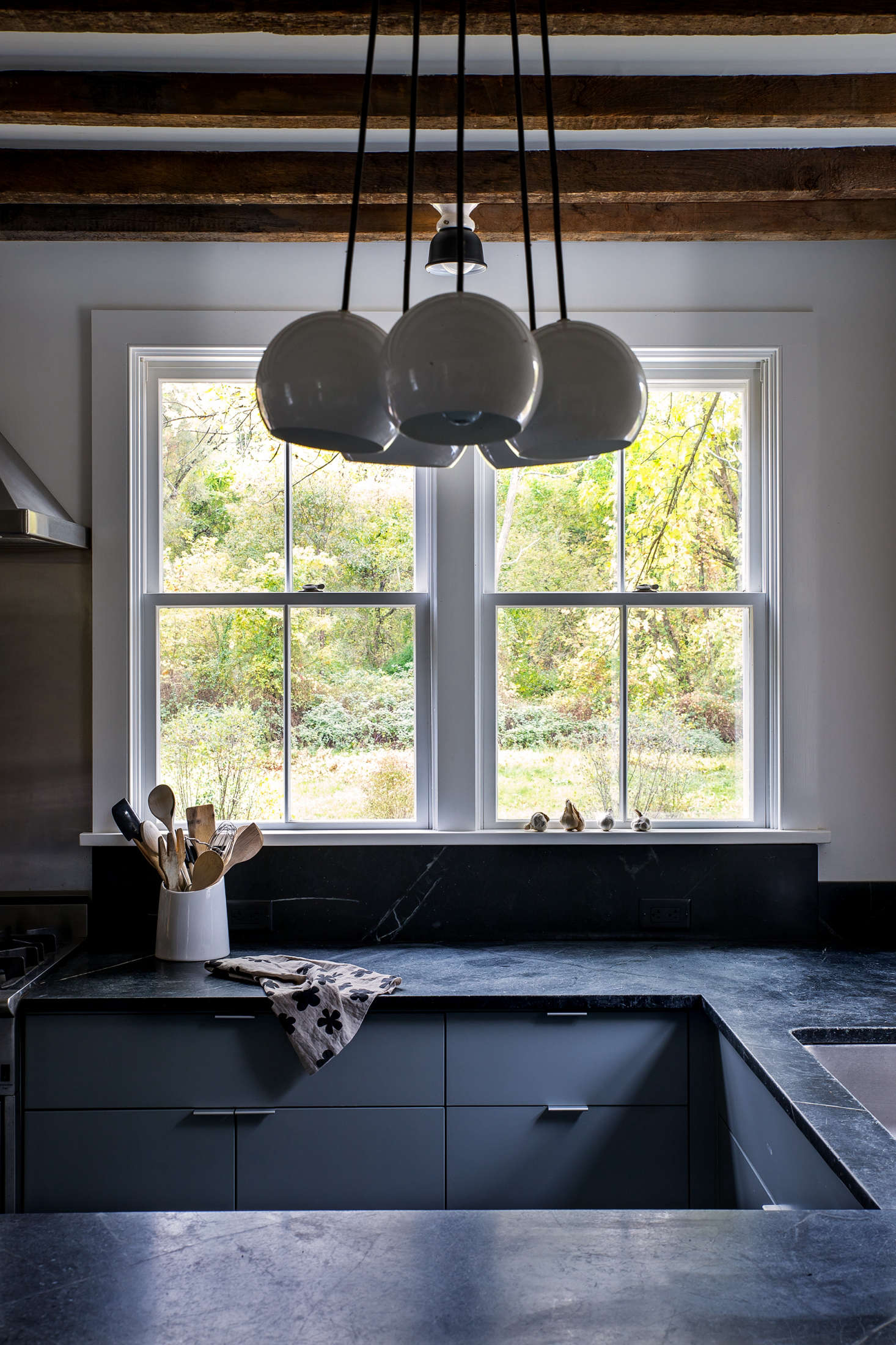Dunja also removed a central island in favor of a U-shaped counter layout. (The tea towel on the countertop was designed by Dunja. Visit her her online shop, Doonyaya, for similar.) A cluster chandelier from Schoolhouse Electric illuminates the breakfast bar.