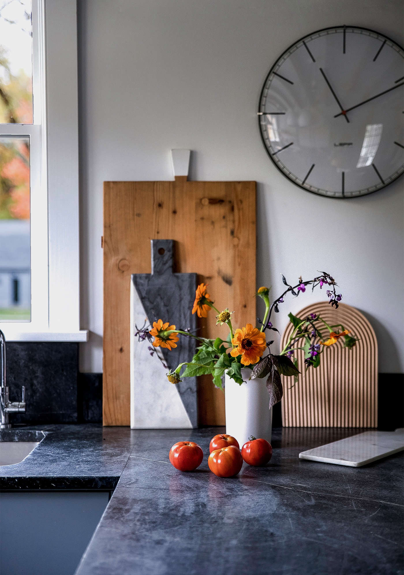 Bounty from Dunja's garden: Tomatoes and flowers add a bit of autumnal color. Against the wall rest a vintage cutting board, which Dunja bought at Brimfield, a two-toned marble board by Jonathan Adler, Hay's Field Cutting Board (available at Finnish Design Shop; $60) and another smaller marble board from Hammertown in Rhinebeck. Leff's Large Index Wall Clock is available at Lumens; $99.