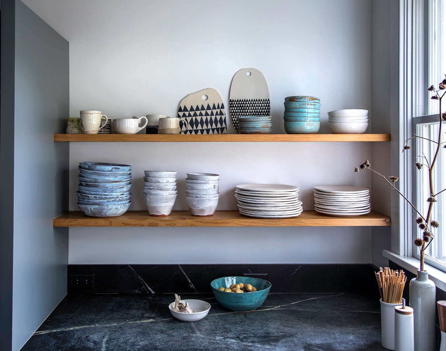 Open shelving holds Dunja's collection of dishes by Tivoli Tile Works. The geometric cheese boards are by Dunja (left) and Mbartstudios (right).
