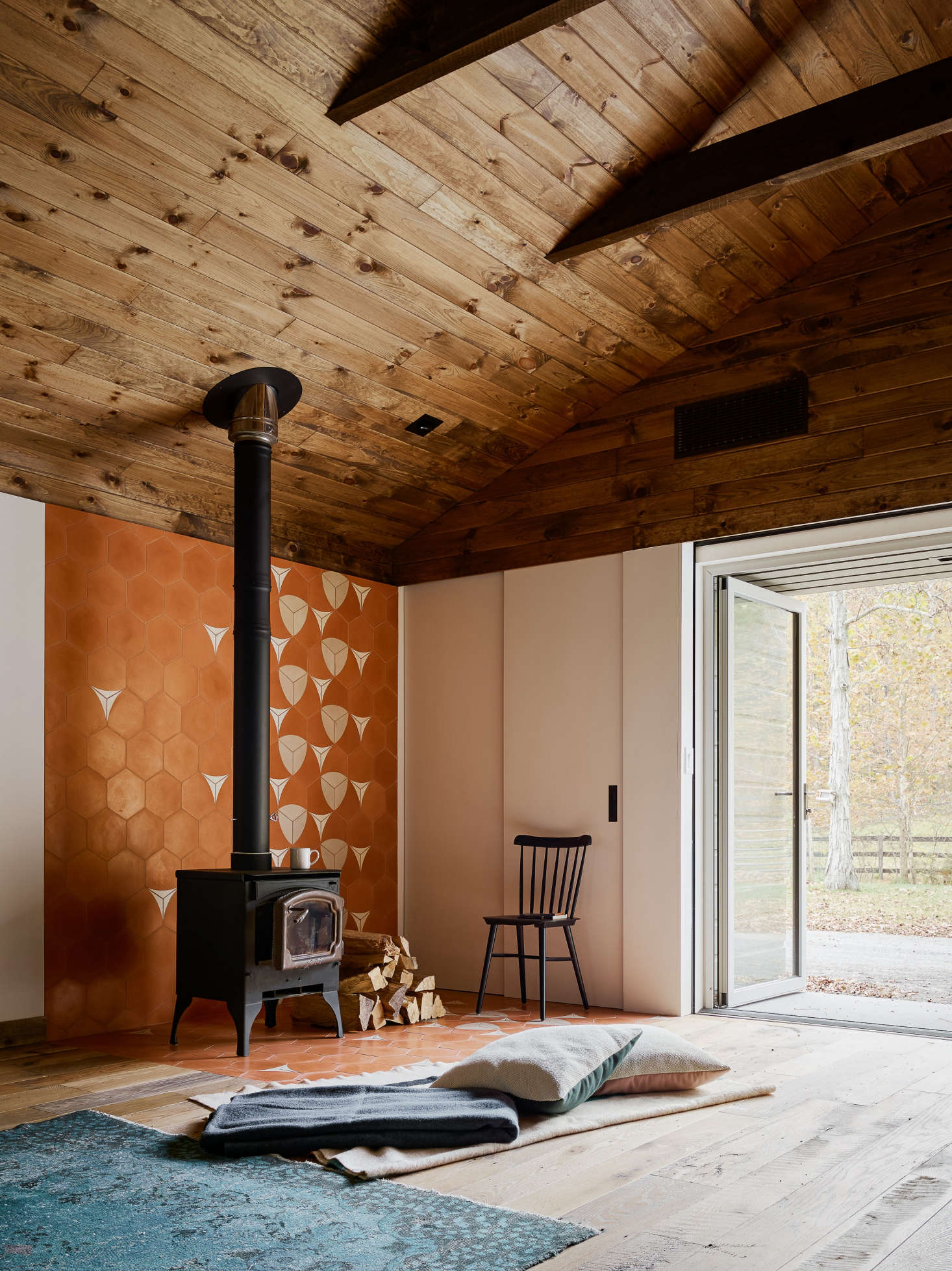"""Adjacent to the sitting area is a woodstove with a tiled back wall and floor. """"We used a bright pattern to define space around the fireplace,"""" said Zames, """"in order to bring in light while still keeping things open."""""""