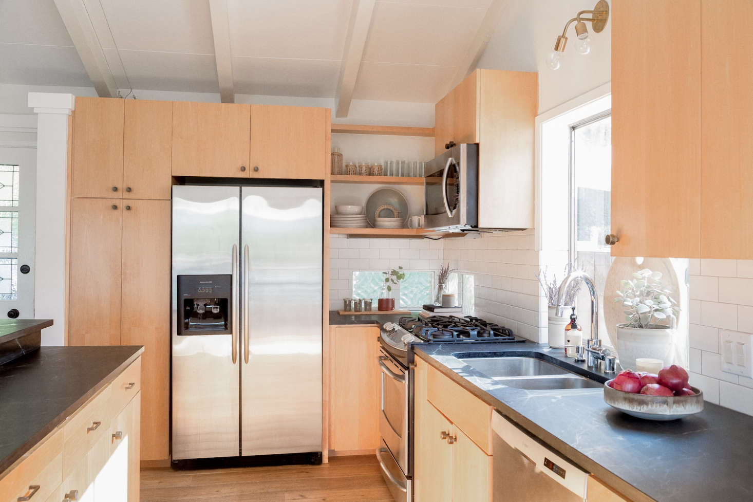 """The couple opted for soapstone countertops, inspired by Remodelista's own Primer on the subject (""""we love the gray color and the natural look,"""" says Hunter). The cabinets were preexisting, and only needed new knobs and pulls."""