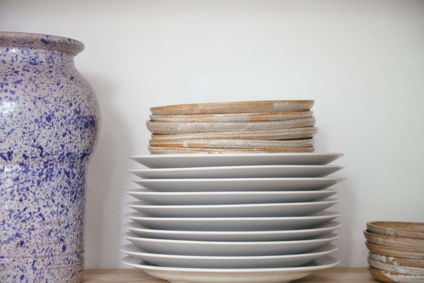 A sturdy speckled vase brought back from Philadelphia and a stack of ordinary white plates mixed with ceramic dishes.