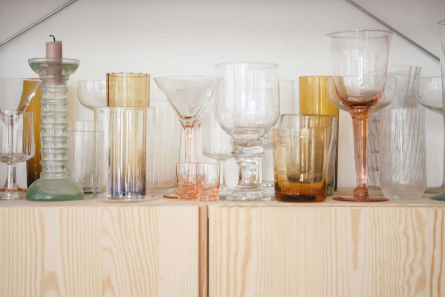 Glassware in shades of amber, pink, and green.