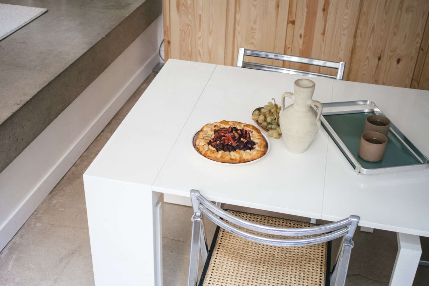 "A fig galette baked by Lucile atop a table of unknown origin that ""folds into a mini console."" The silver tray was Michel's, and Lucile's sister Clarisse bought the chairs from a Belgian antiques website."