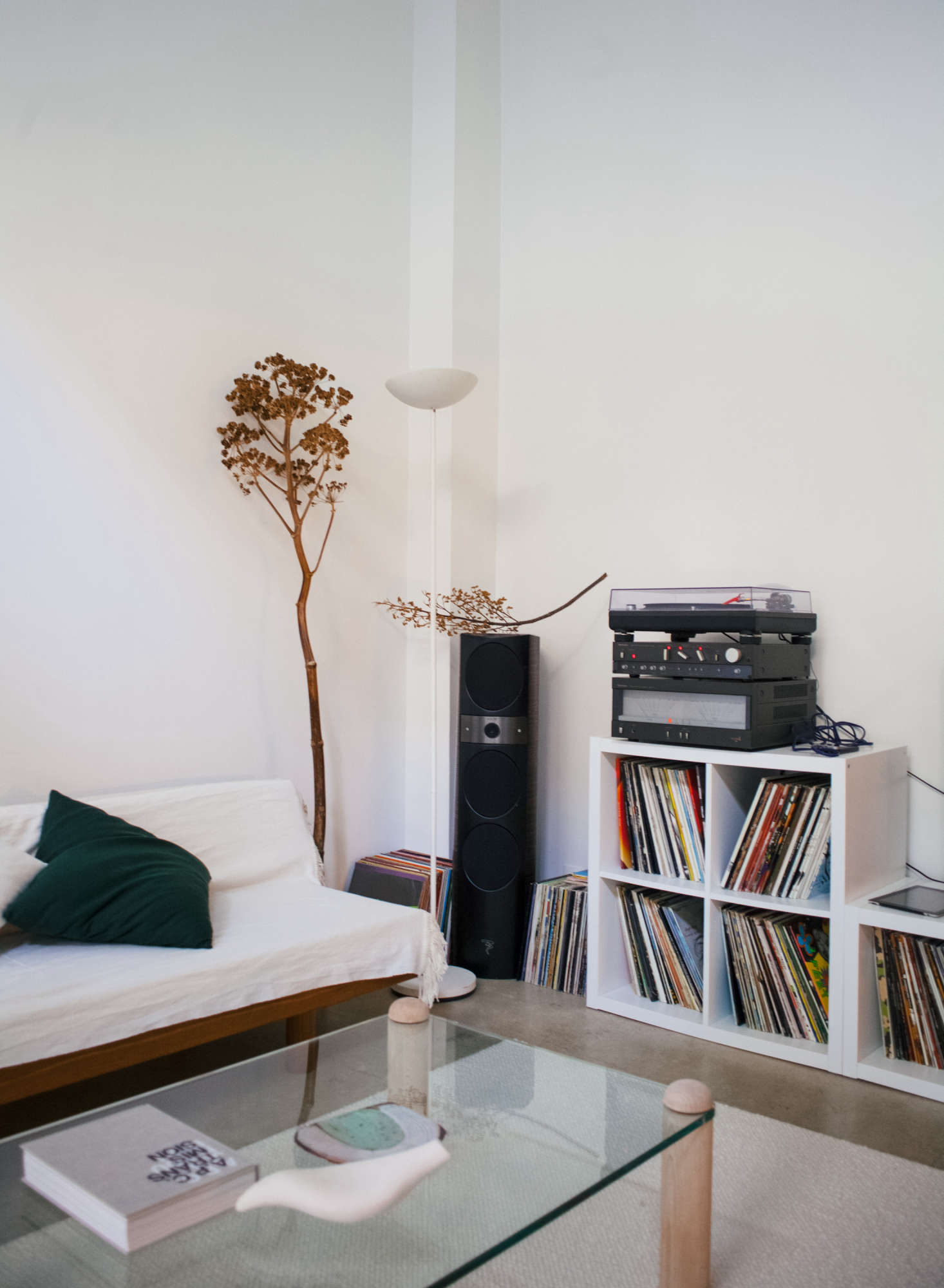 A 90s halogen floor lamp of Michel's illuminates a corner; the speakers are from Focal and the turntable is a Technics src=