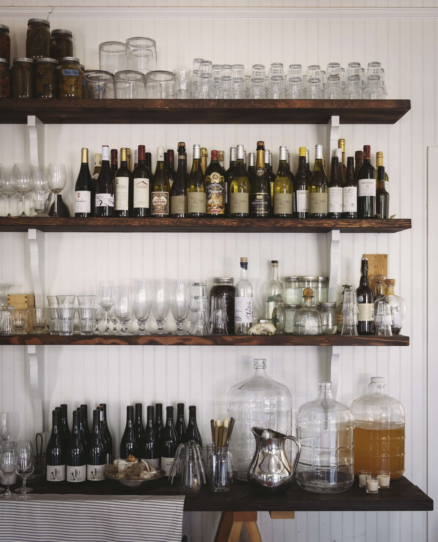 Wines and wine glasses mingle with spirits, vinegars, and pickled vegetables on the cookhouse&#8