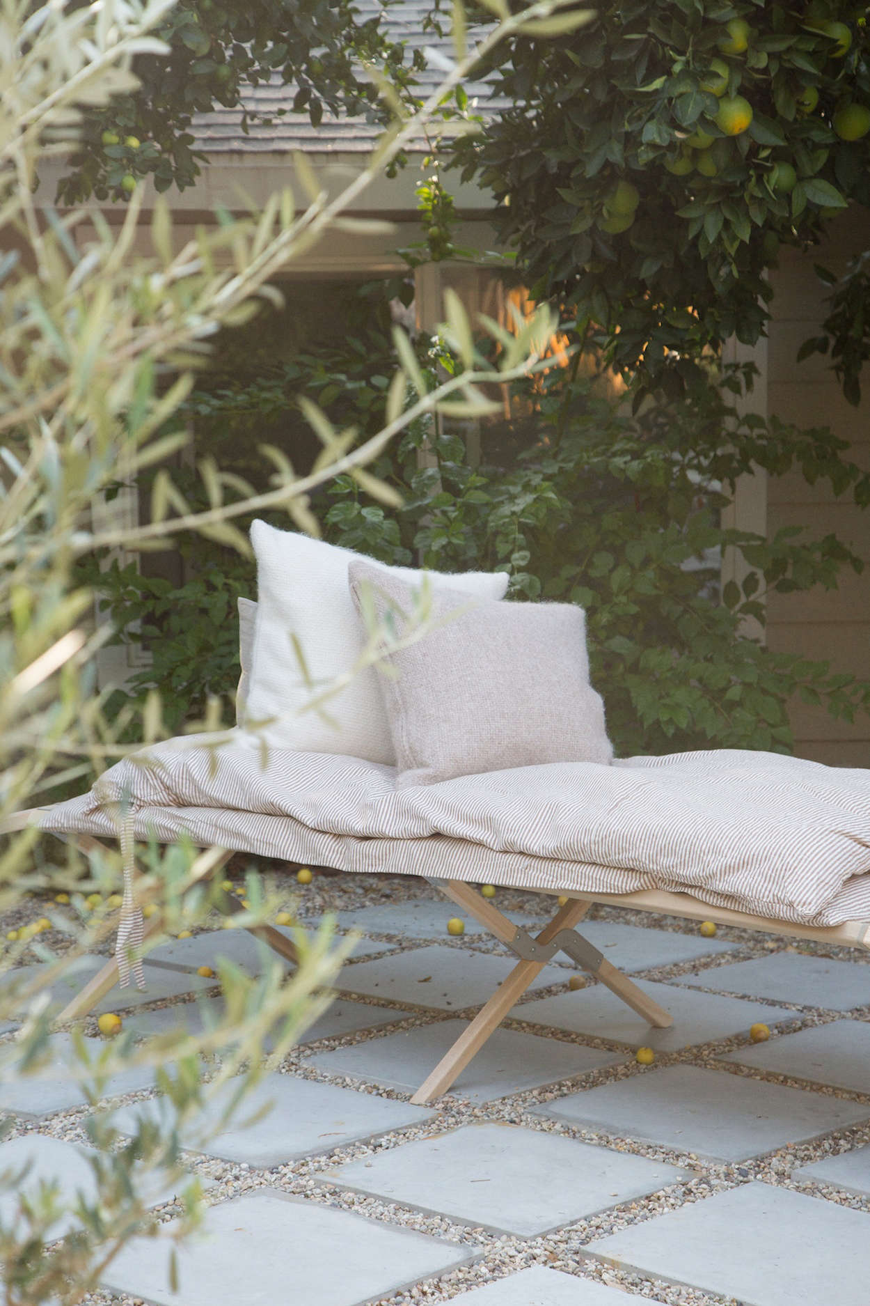 """When they bought the house, says Hunter, the outdoor space """"was filled with AstroTurf andbougainvillea."""" Now, the yard has citrus trees and an informal patio of concrete pavers and gravel. On the daybed, with the alpaca pillows: A Striped Linen Duvet (a collaboration between Jenni Kayne and Parachute); $349 for full/queen duvet with two shams."""