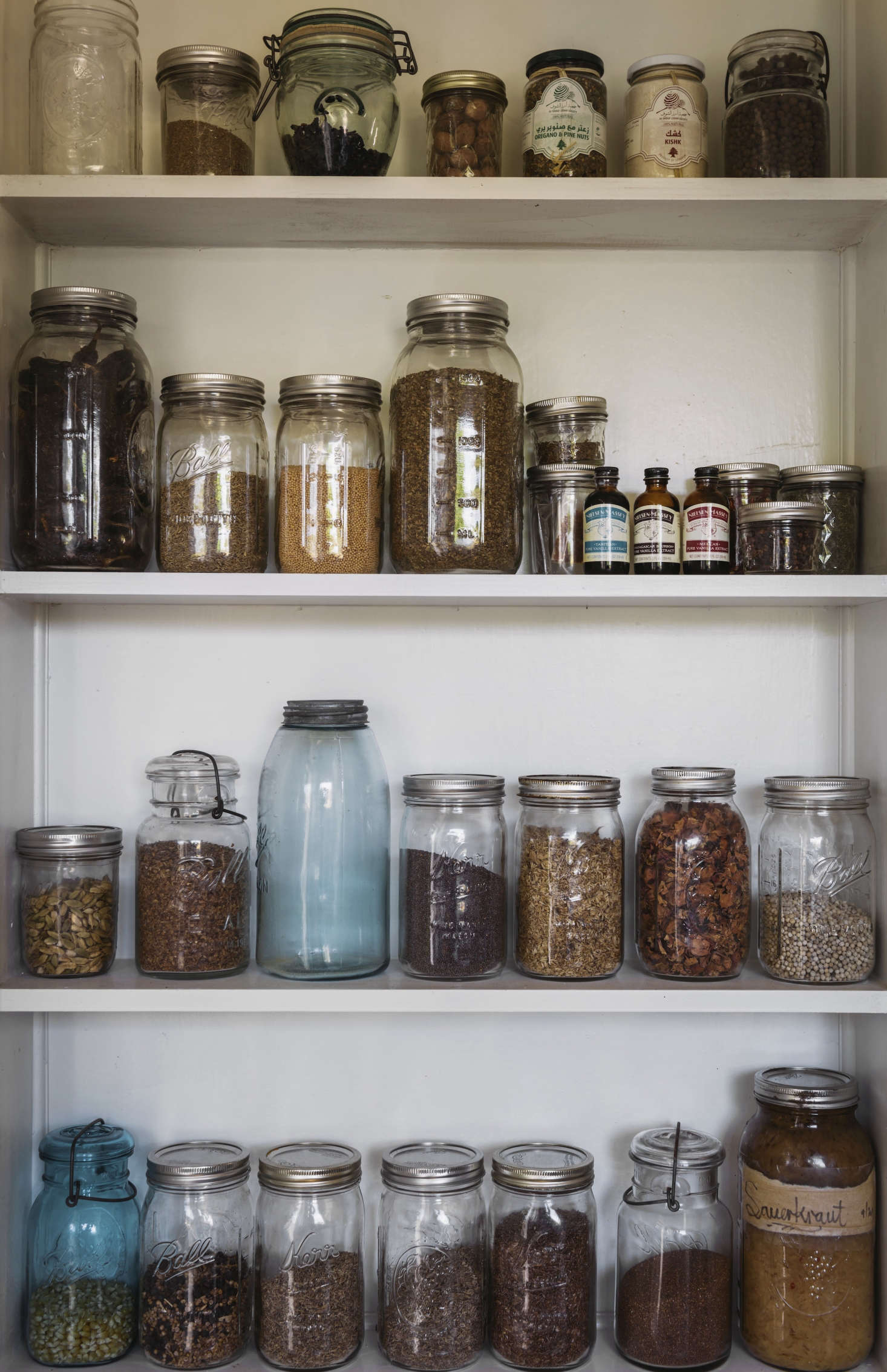 A pantry shelf behind the sink holds dried herbs, spices, grains, nuts, and even house-made sauerkraut.