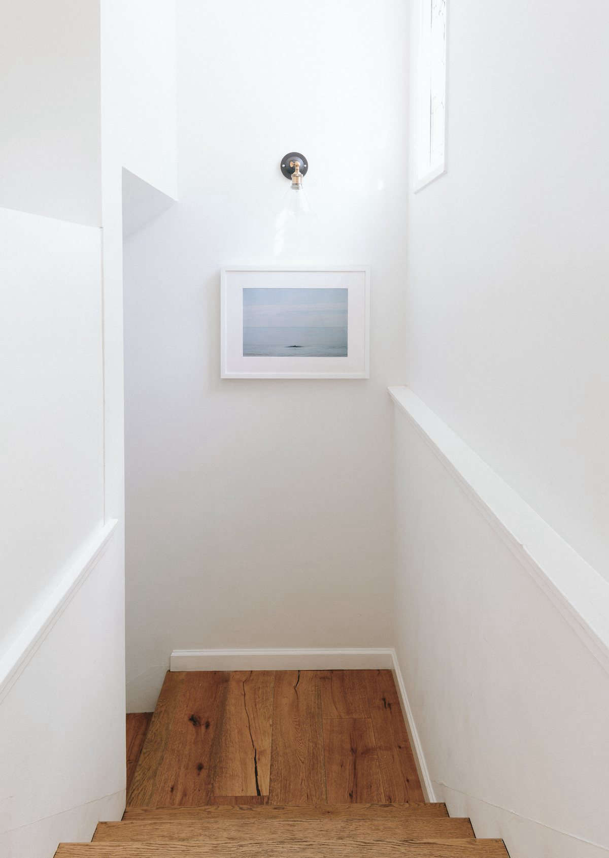 The artwork in the stairwell is an Emma Wood Print by photographer Marc Gabor—a collaboration between Jenni Kayne and Tappan ($655, framed). Hunter found the sconce on Amazon. The floors throughout the house are brushed white oak.
