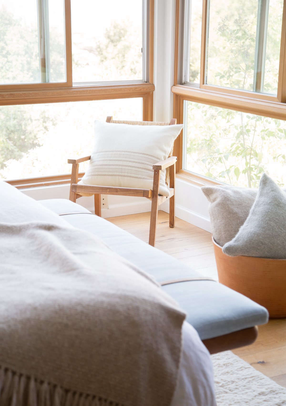 A leather basket from Jenni Kayne stores more alpaca basketweave pillows. At the end of the bed is a vintage wood bench from Lawson-Fenning in LA, covered in blue linen with added leather straps.