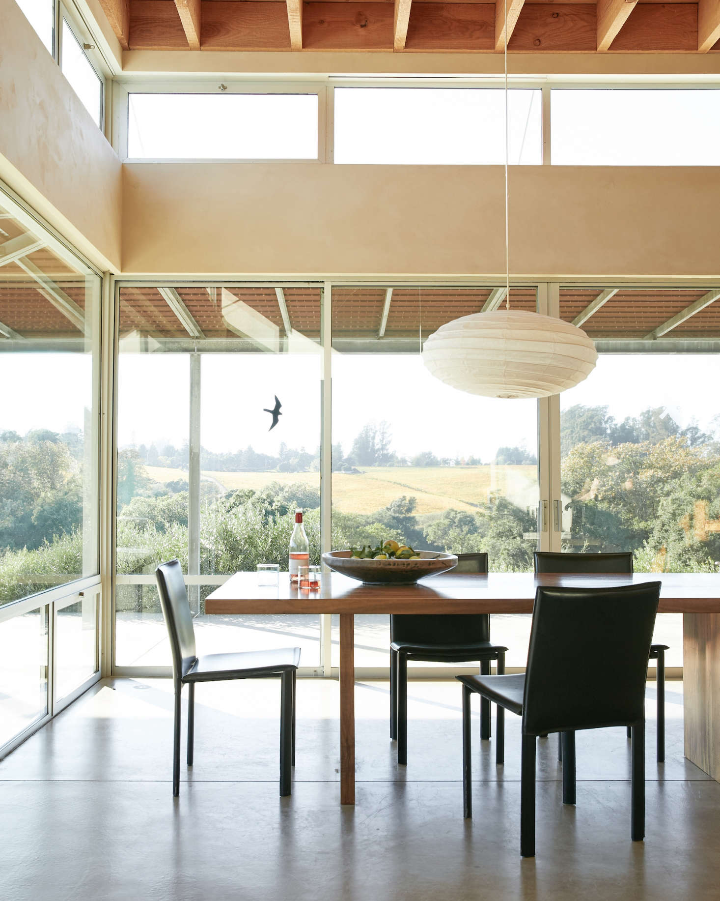 Next to the kitchen is the open-plan dining room, perched on the edge of the upper estate overlooking the vines. The dining table was custom-designed by Anding, fabricated locally using salvaged wood.