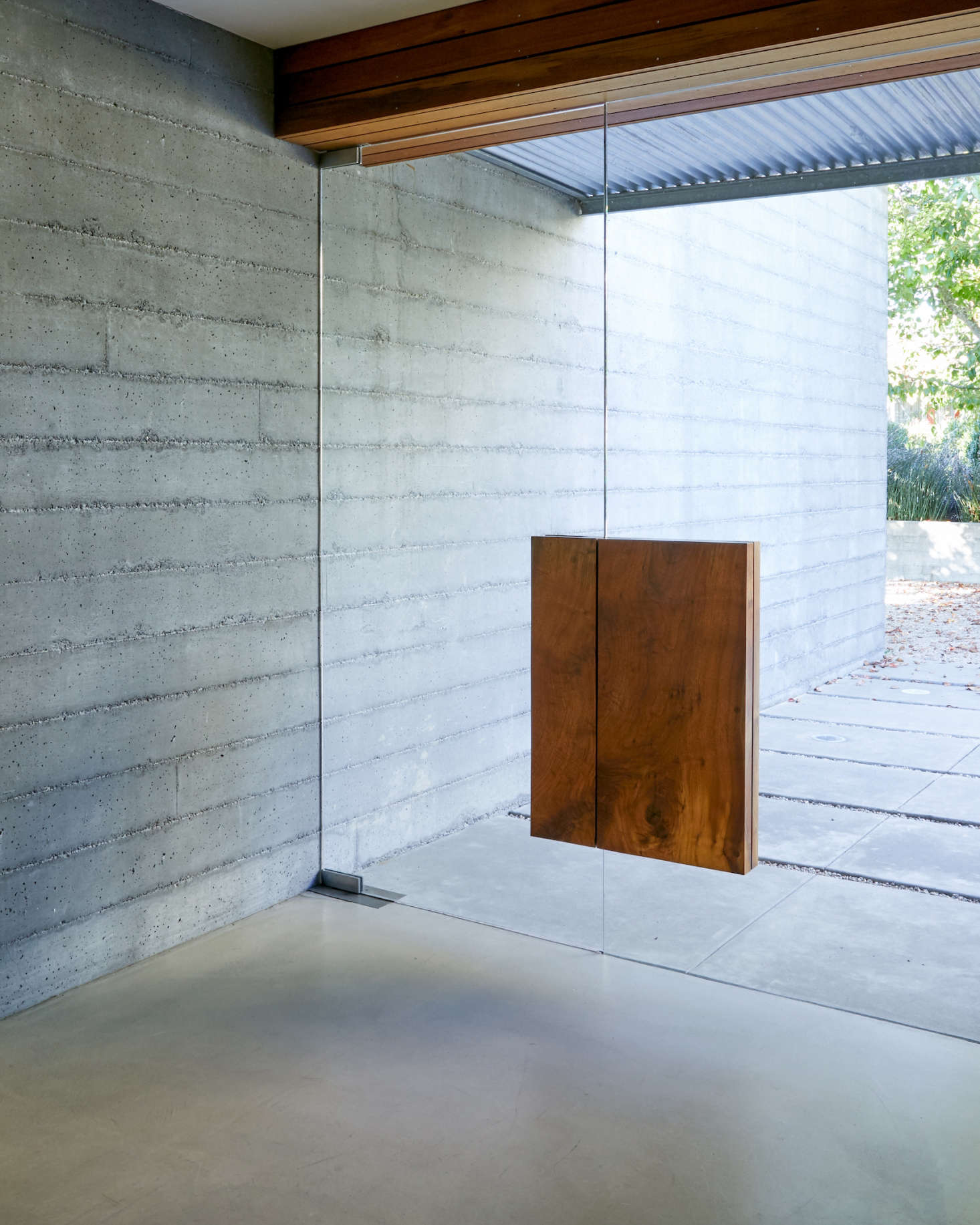 The front door is made of two glass panels, each with a block of claro walnut wood &#8