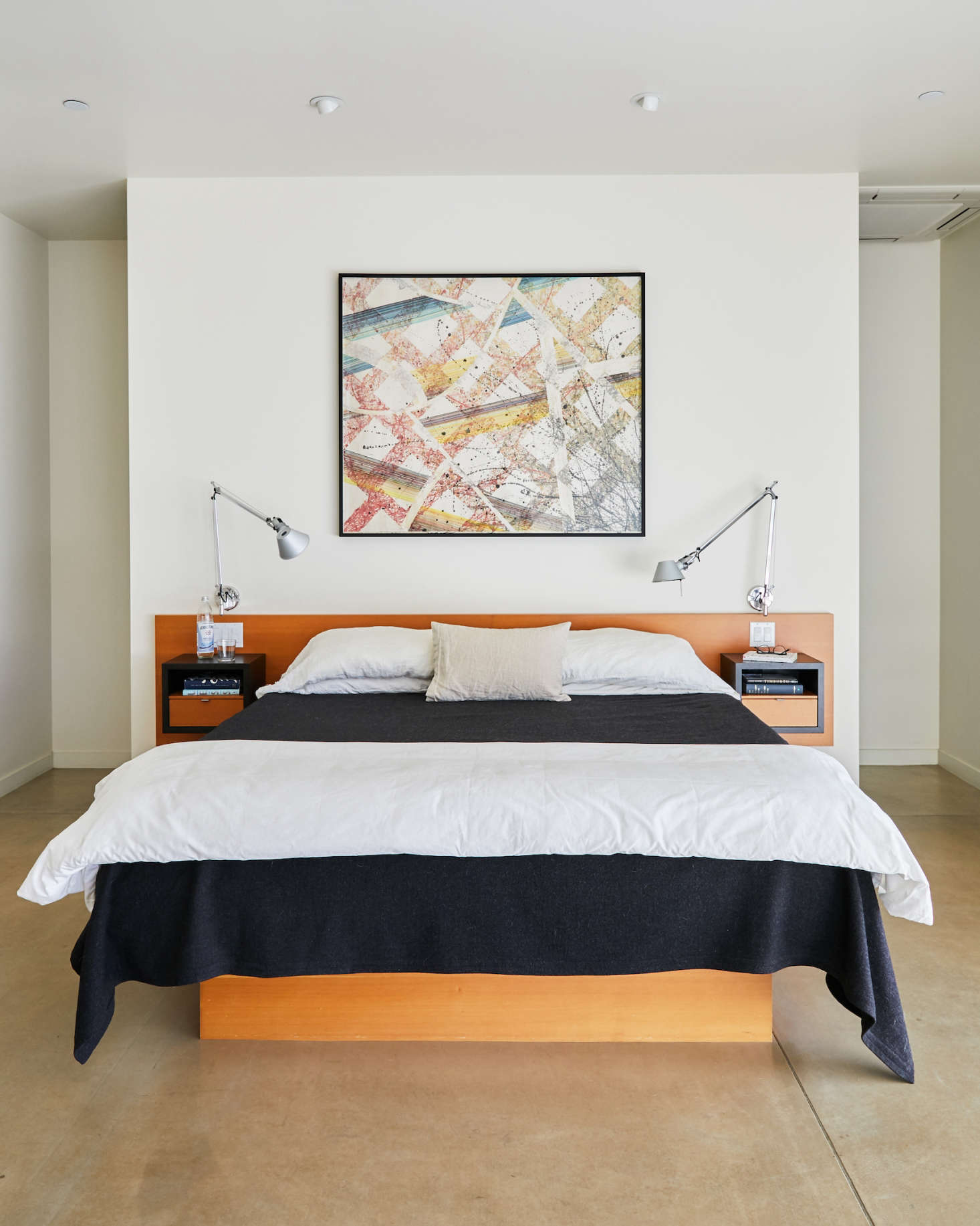 In the master bedroom, Anding designed the custom bed with integrated nightstands. The painting is by Stephen Singer, and lights flanking the bed are Tolomeo Classic Wall Lamps.