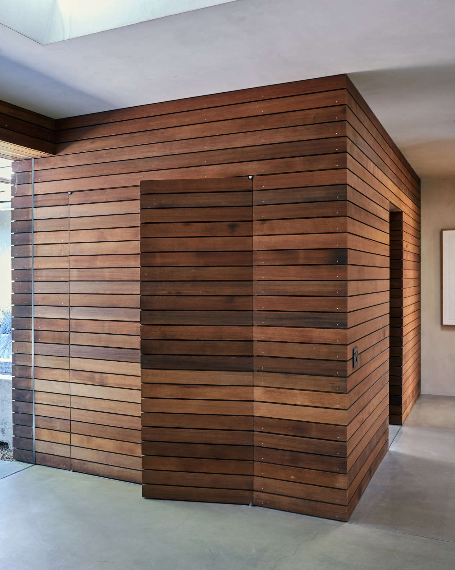 Off the foyer is a utility room (with mudroom and closets) paneled in repurposed wine-barrel redwood that extends continuously from the exterior of the house. Coat closet doors are fully integrated into the paneling: &#8