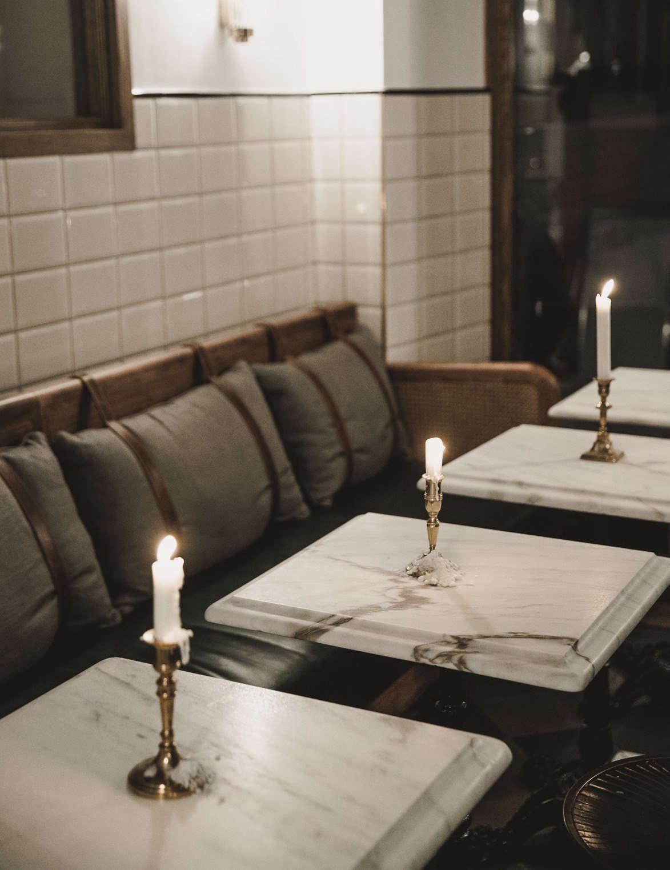Single brass candlesticks adorn each table—an idea to copy at home.