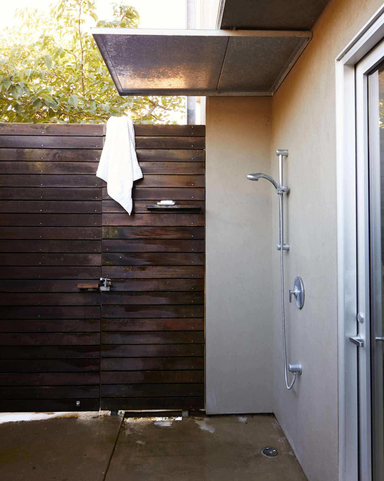 An outdoor shower lined in stucco and redwood off the back door from the master bath.