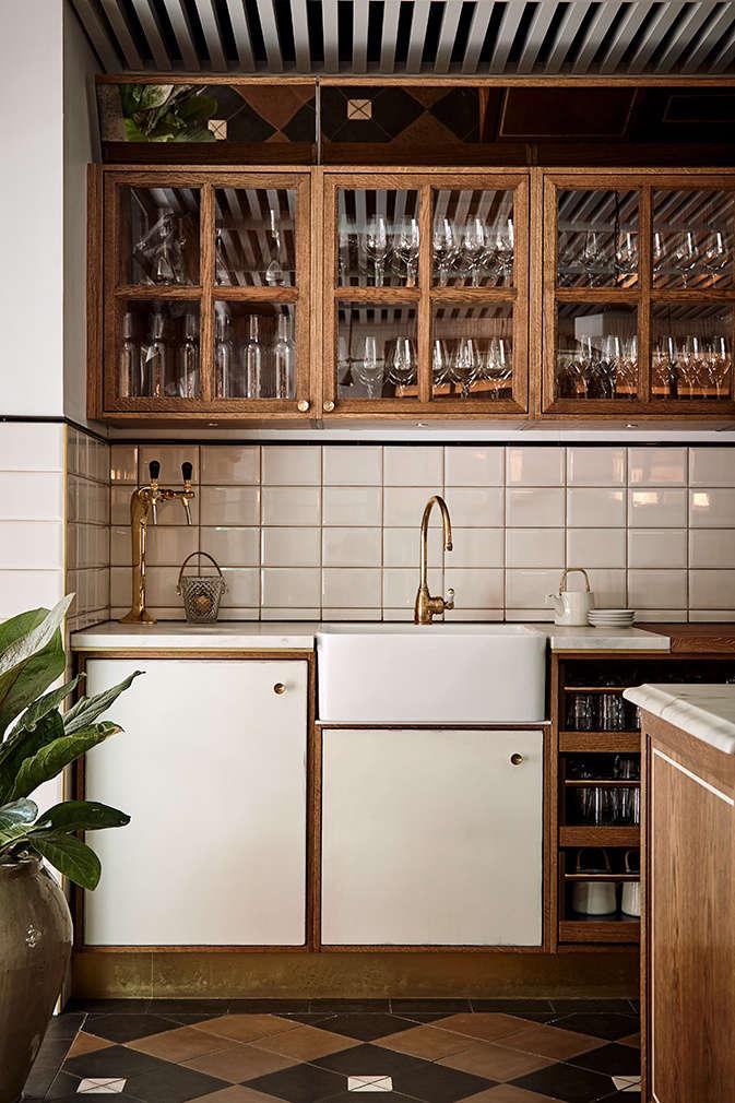Glassware stocked behind the bar, and a backsplash of oversized white tile.