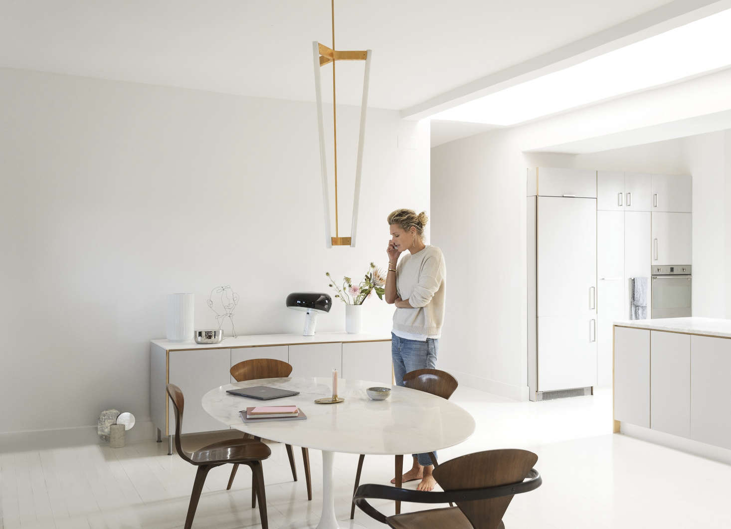 """A long entry hall (with her children's rooms and a bathroom off it) leads to a large, open living and dining space. Camilla gave the loft the Scandi treatment by whitewashing the walls (""""in a universal white, matte, of course"""") and floor (""""a high-gloss epoxy, like a nautical paint, that can take the place of rugs"""")."""