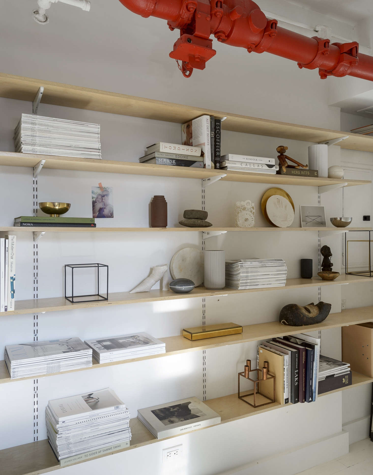 Plywood shelves built from hardware store parts display not only books and magazines but also favorite souvenirs and gifts, including a vintage Kay Bojesen Teak Monkey that Peder's grandmother brought for them when she was 90. Read about the copper cube candleholder in The Kubus Goes Glam.