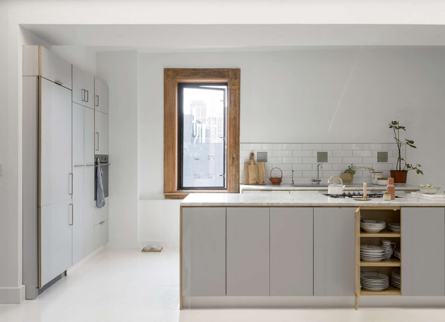 The apartment came with its streamlined kitchen, which Camilla says is composed of Ikea cabinets with custom fronts of pale gray laminate. Next to the sink, the terracotta planter and Edge Teapot, are by Skagerak (Objects by Camilla Vest serves as the Danish brand's exclusive US wholesaler). The Kaico Kettle is by Shoei Kogyo of Japan.