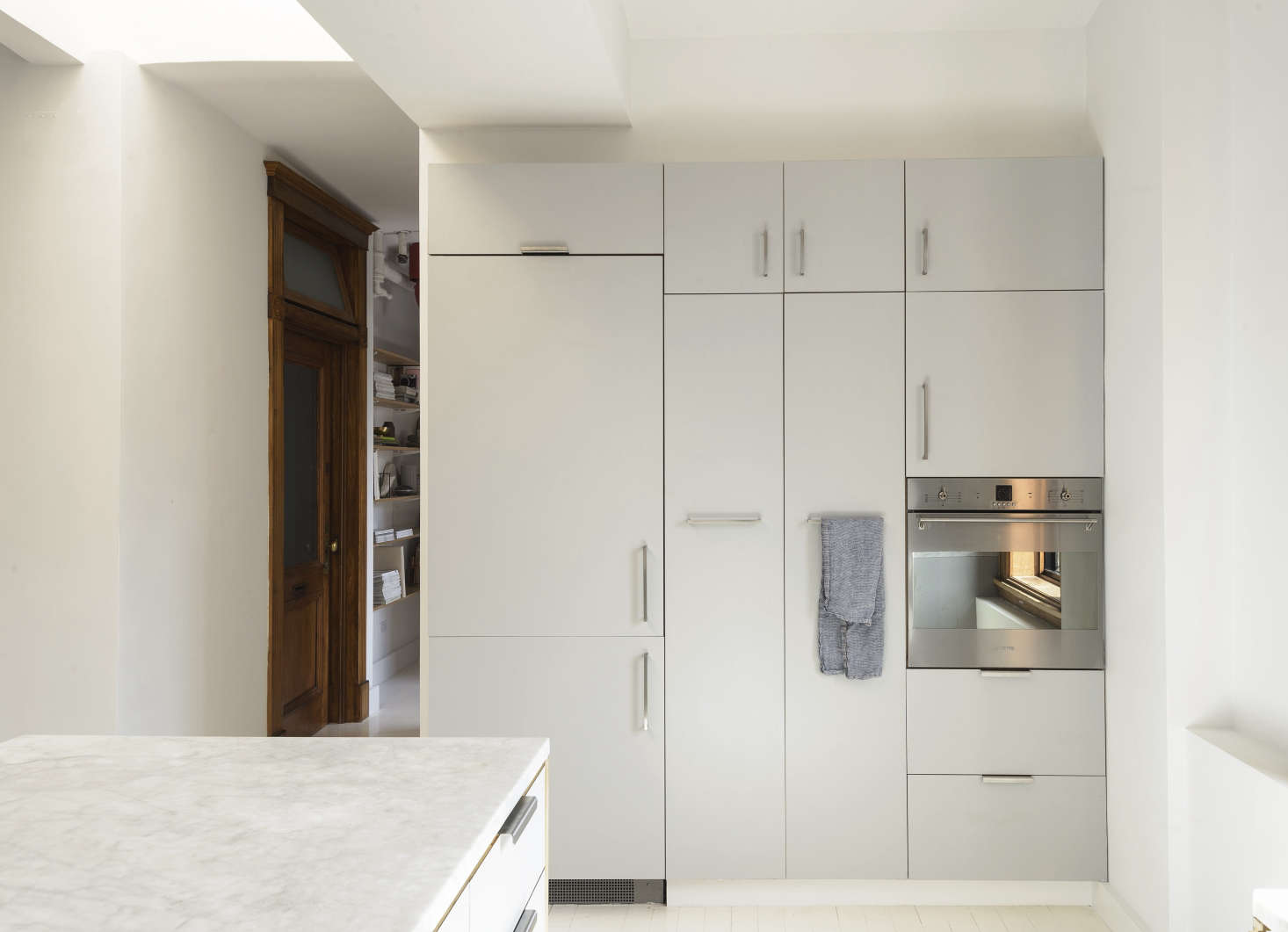 The fridge is concealed on the cabinet wall, which incorporates a Smeg wall oven.
