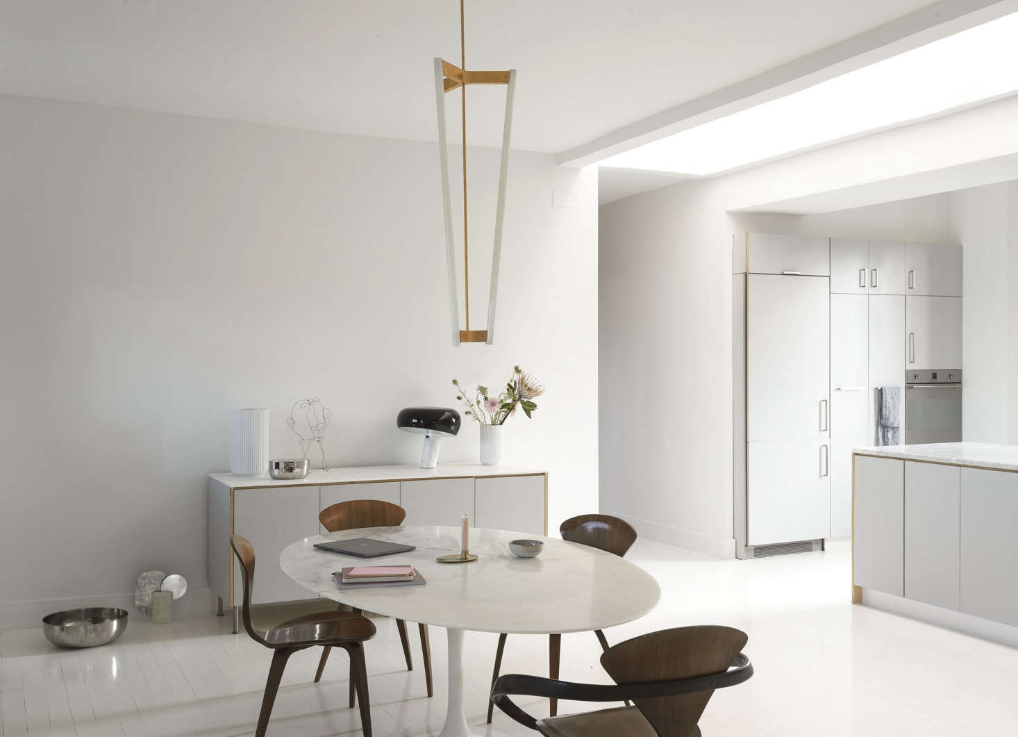 """The black-and-white light on the sideboard is the FlosSnoopy Table Lamp (Camilla purchased it in Italy and checked it with her luggage). The pendant light is British designer Michael Anastassiades'sTube Chandelier (""""He's a genius. I checked that too—I have a lamp fetish""""). The silver bowls are Georg Jensen designs that move around—the large one was a wedding gift from Peder's parents."""