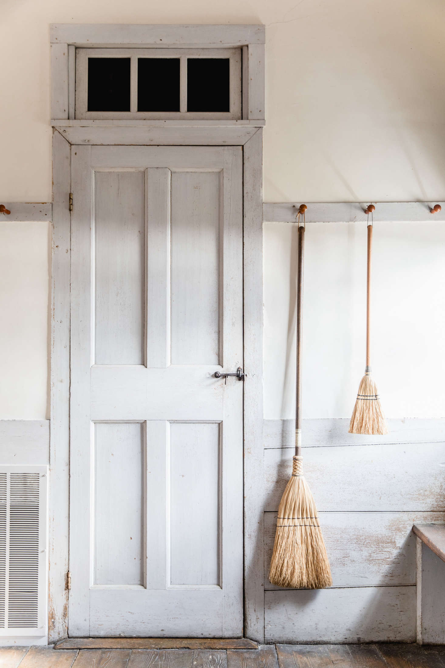 Peg rails keeps brooms at the ready in a Shaker schoolhouse. See In the Dwelling House: 16 Design Ideas to Steal from the Shakers.