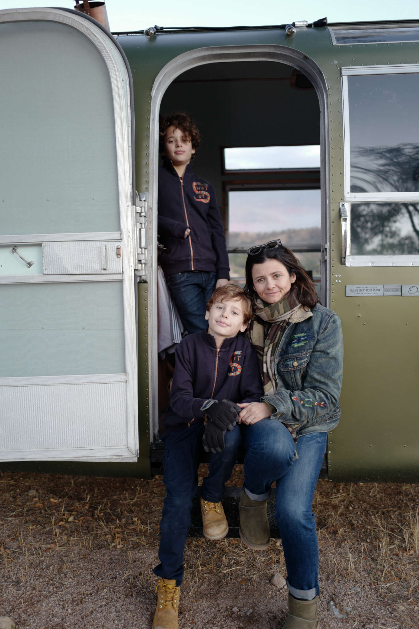 """Anne-Marie and sons at the trailer's entry with its original screen door. Jorge loves old airplanes and notes that """"the rounded door has that kind of feel."""""""