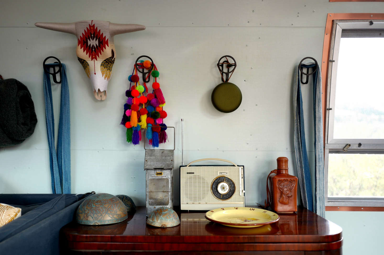 The interior walls and credenza top are painted a subtle mint that Jorge notes is two shades lighter than the classic Land Rover color. (Land Rovers are another of his passions.) Circular bronze sombrero hooks–Gancho de Bronce Modelo Aro from Mexican hardware company Counter Cultures—are used as catchalls.