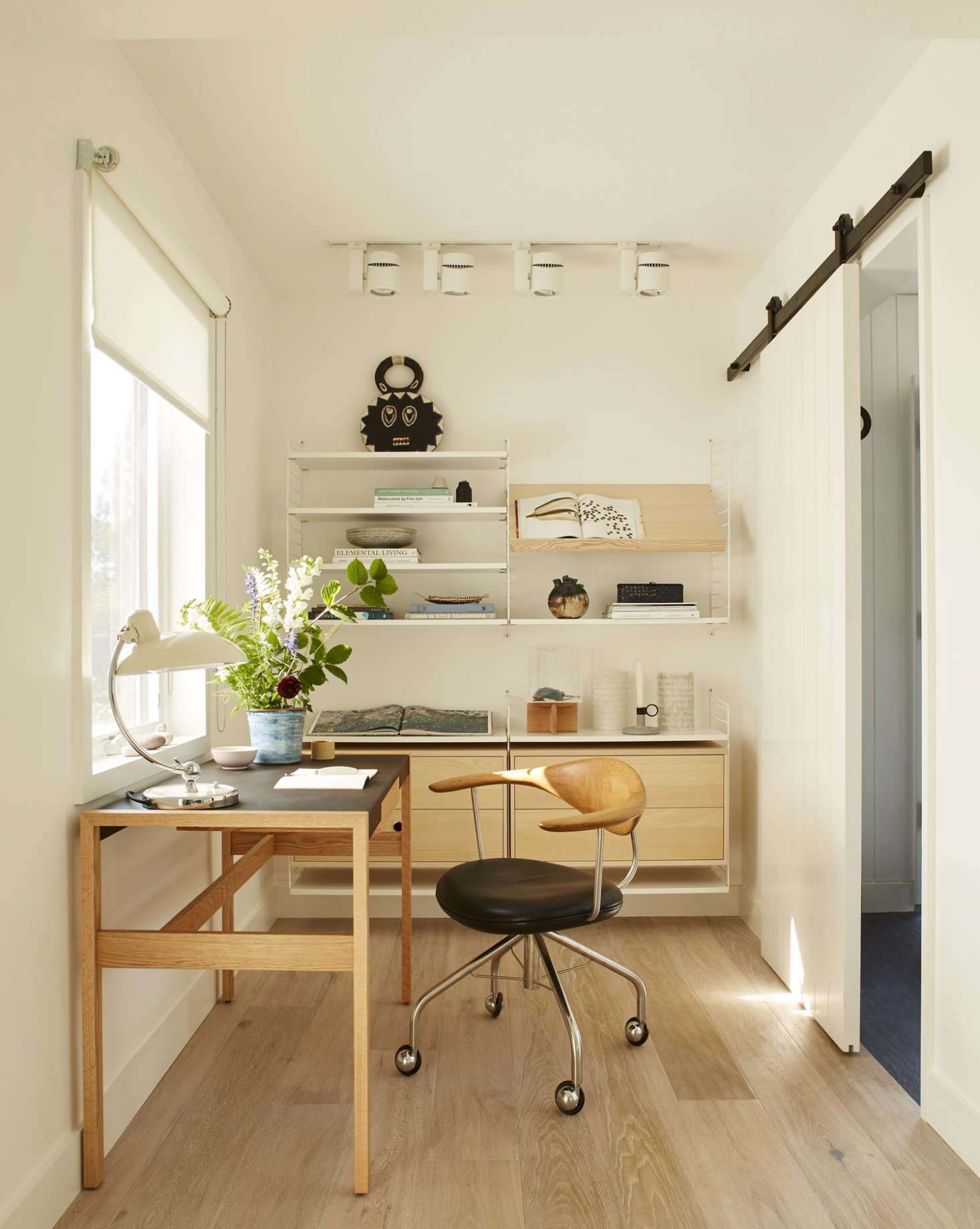 Wall-mounted String Shelving provides both open and closed storage options in this office designed by Ellen Hamilton. Photograph by Max Kim Bee, from A Modest Beach Cottage on Martha&#8