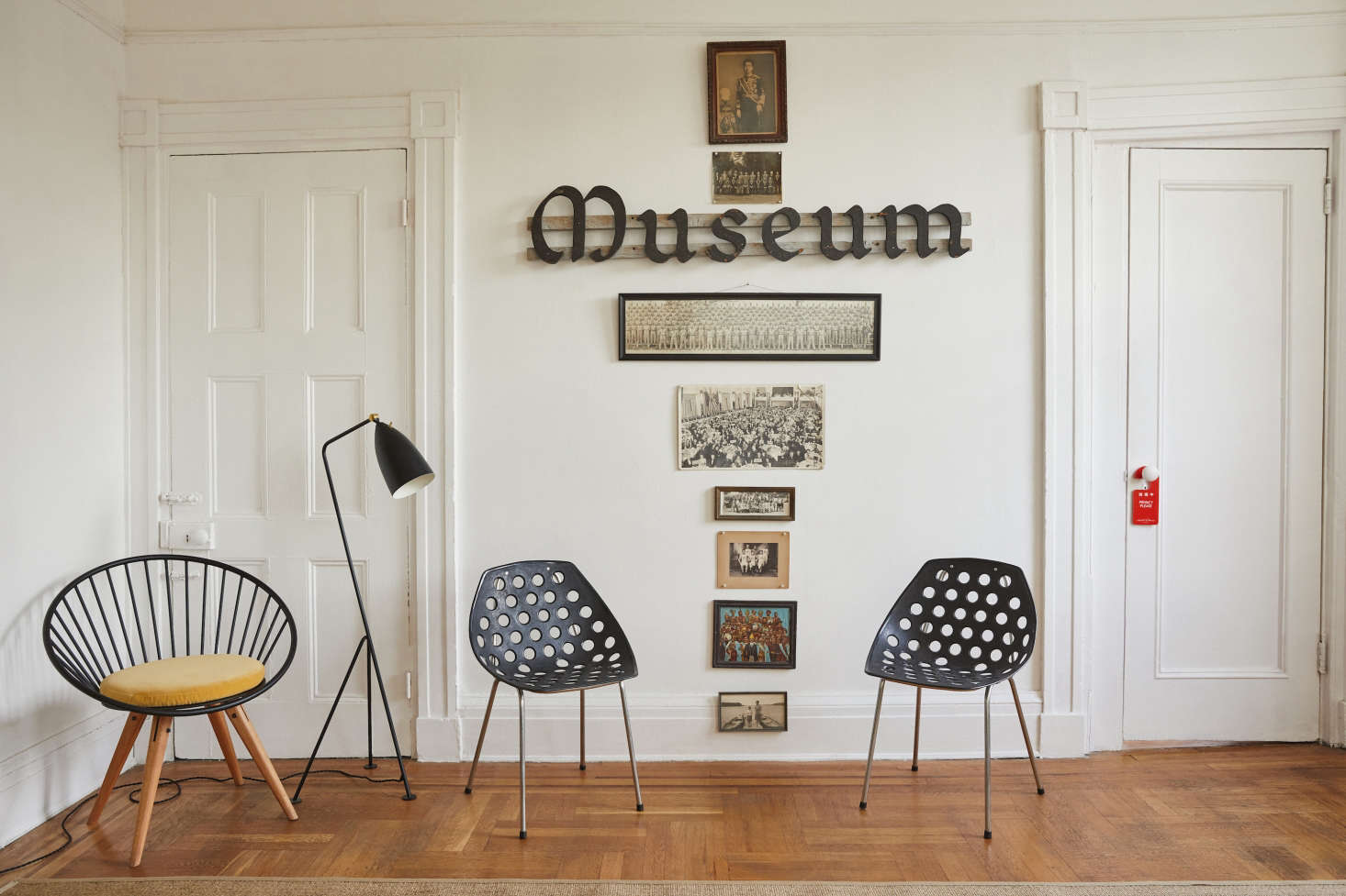 """Mounted on the wall is a museum sign Valentin got from a friend, conceptual artist Cyril Duval of Item Idem. The photos below are all group photos taken from the 1930s to 1960s collected, he says, """"from past lives in Paris, Tokyo, London, and Los Angeles."""" In front is theBogus Studio Circle Chair, aGreta GrossmanGrässhoppa Floor Lamp for Gubi, and two 1960sCoquillage Chairs by Pierre Guariche for Meurop."""