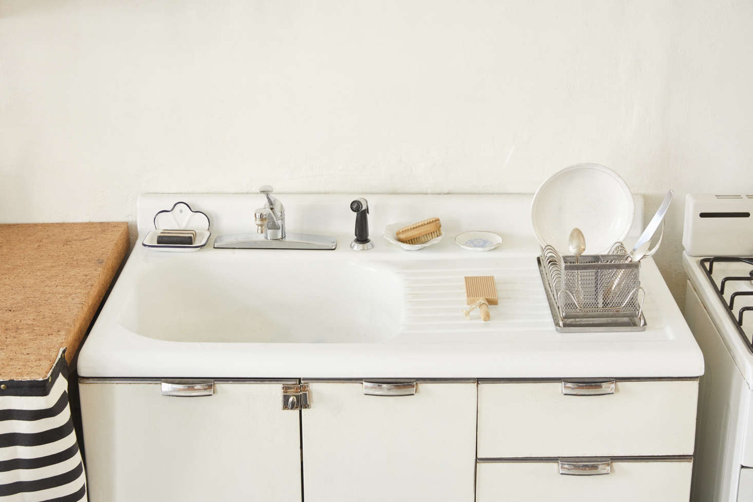 The vintage enamel and metal sink cabinet is outfitted with anEnamel Soap Dish and a Polder Stainless Steel Dish Rack. The dishes are fromAstier de Villatte and thewoodGnocchi Board is, improbably, from Bed, Bath & Beyond.