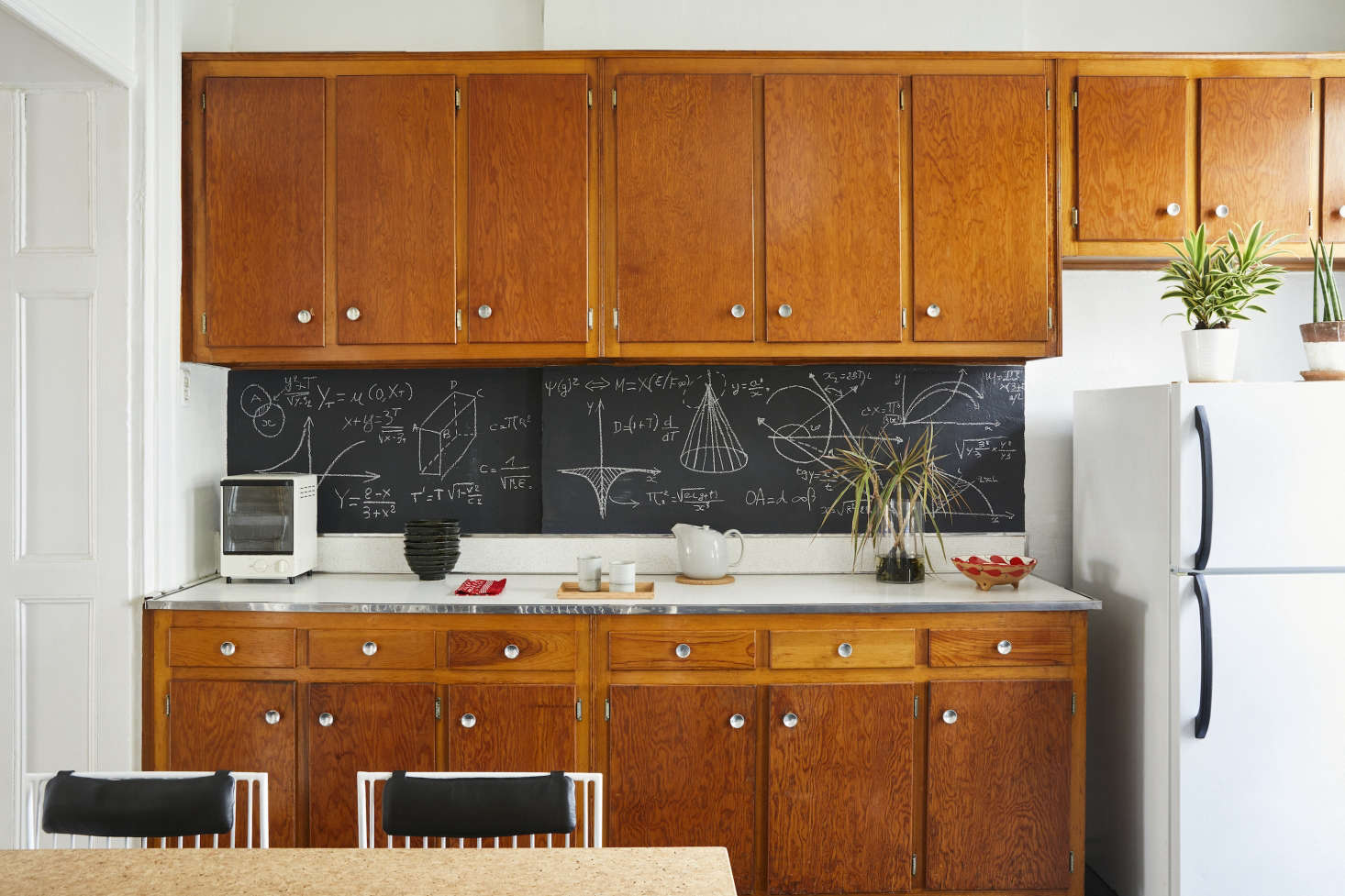 """The kitchen is a room of unexpected details. Valentin created a DIY backsplash using a slab of wood painted with chalkboard paint. Using chalk, he created a diagram of mathematic formulas that """"contributes to the kitchen's investigative effect."""" The toaster is aMuji Vertical Toaster Oven that, along with the ceramic dishes and furoshiki cloth, Valentin bought while living in Tokyo."""