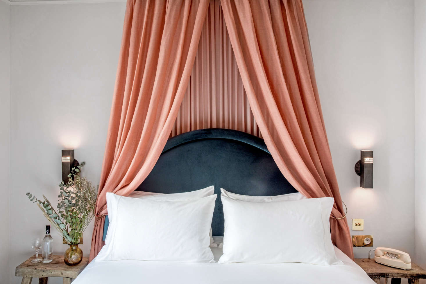 A lush salmon-colored canopy frames the bed (and dark-blue velvet headboard) at the Grands Boulevards Hotel in Paris. See more of the dramatic guest rooms (each with a touch of pink) in Beds Take a Bow.