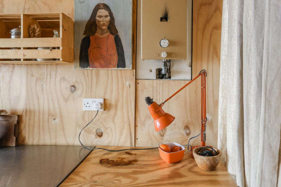 The hut is mostly plywood, but Maria and Durrell incorporate a playful palette of orange, red, and green when they can. Photograph by Marcia Mihotich from Two London Creatives Shore Up a Tiny Beach House, Ikea Hack Kitchen Included.