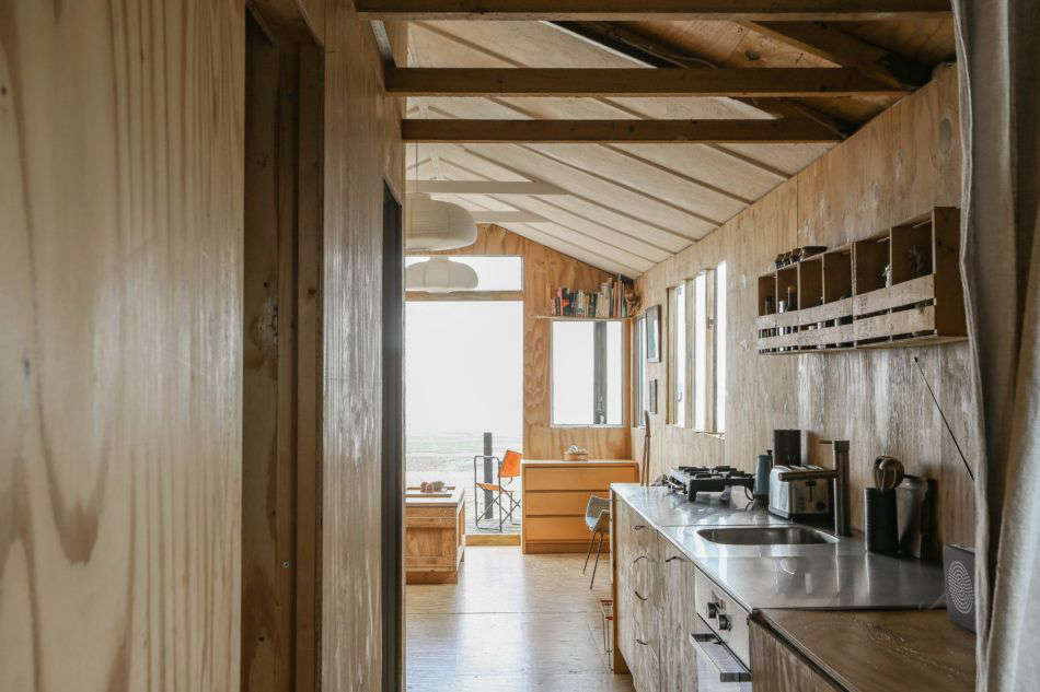 The view from the back of the house, through the kitchen, and onto the deck. Photograph by Marcia Mihotich from Two London Creatives Shore Up a Tiny Beach House, Ikea Hack Kitchen Included.