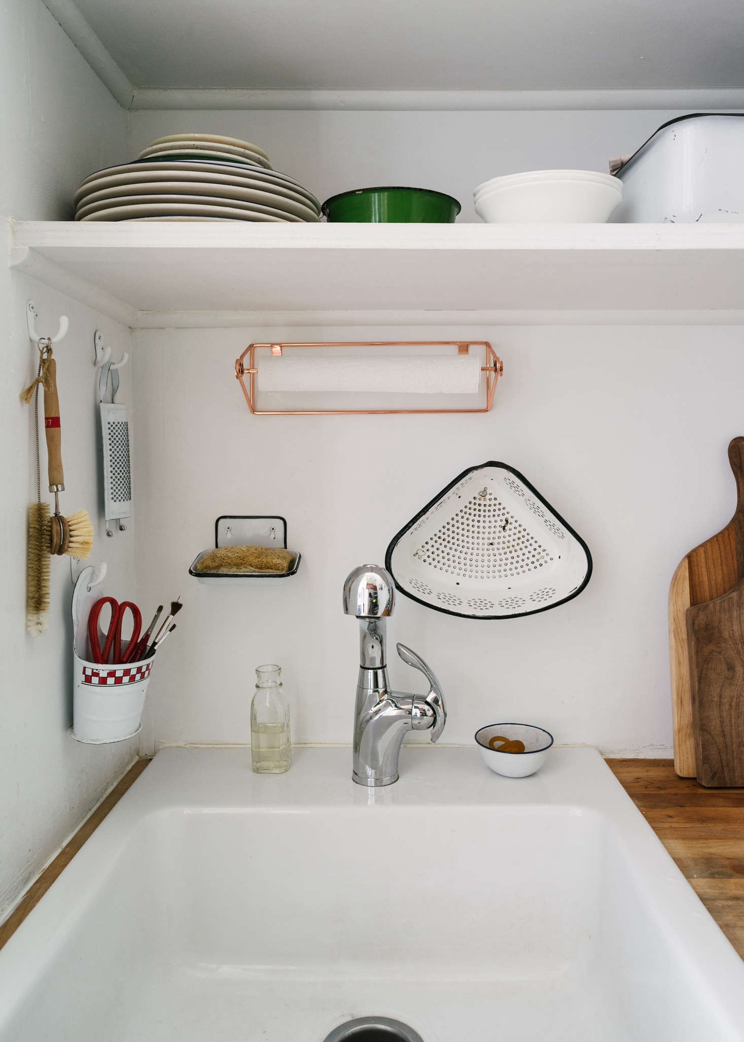 """I had no interest in enamelware until I met Carson,"" says Sandeep. ""He grew up with so much of it in the South, and I realized it was a big part of my own visual vocabulary from England. So now we're both obsessed."" Surrounding the sink is a collection of enamelware—a grater, a wall bucket, soap dish, and strainer—from various flea markets. Paper towels are kept in a Copper Wire Mountable Towel Holder from West Elm and the sink—""a triumph; so affordable and the look and size is perfect""—is the Domsjö from Ikea."