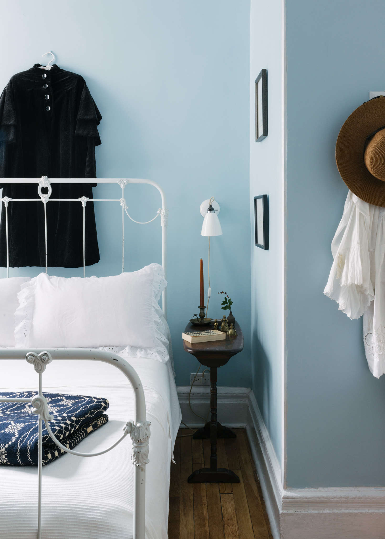 """I always wanted a Wedgwood Blue bedroom, but in reality, Wedgwood Blue proper was a little too dark for this room so we went with Farrow & Ball Parma Gray,"" she says. ""It's a soothing color and reminds me of the last stanza of ""High Windows""  and Marie Antoinette all at once!"" The wrought iron bed frame is from a Goodwill in New Jersey with Stonewashed Belgian Linen bedding from Restoration Hardware. Behind the bed is a velvet overcoat from Sandeep's grandmother: ""very austere, as I believe she was."""