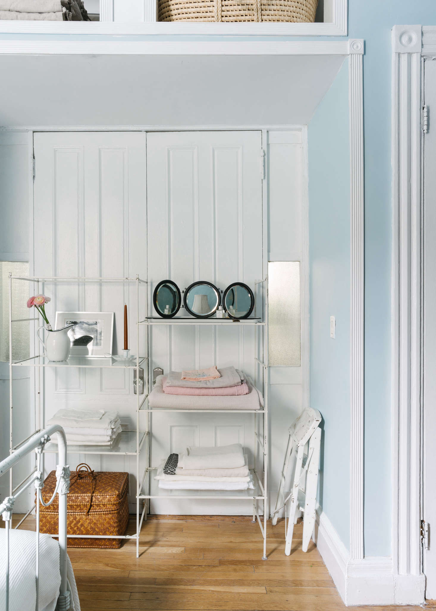 A glass shelf bought on a whim at ABC Carpet & Home (something similar is the ABC DNA Synthesis Shelf) stores linens in a French door alcove between the bedroom and living room.