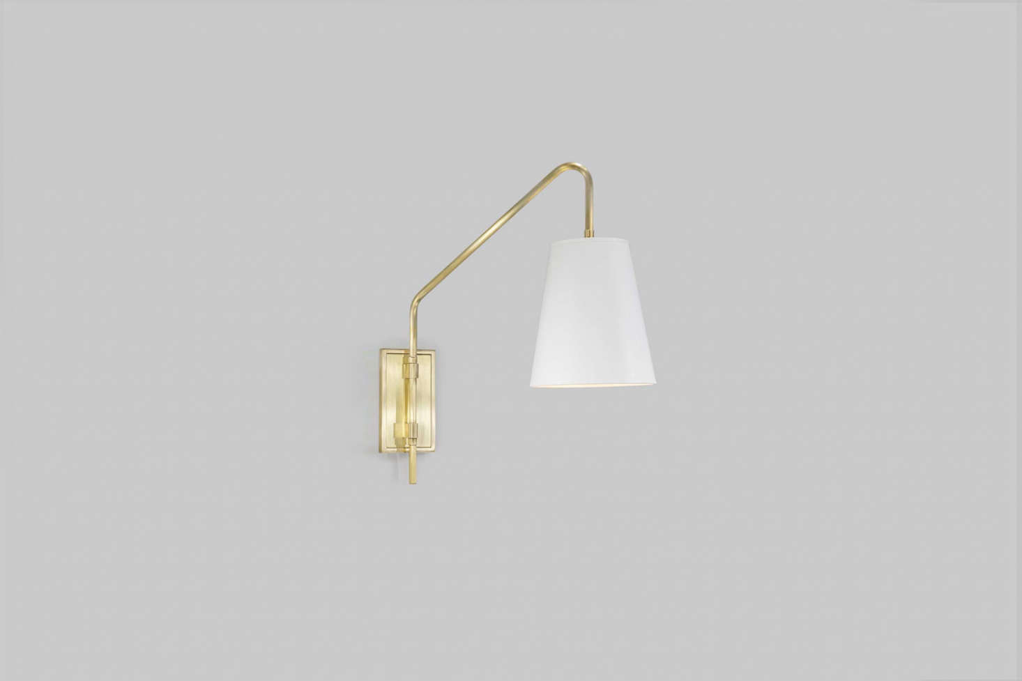 A similar light to the custom fixture by Urban Electric Co. above the bathroom console is their Audley Sconcein Antique Brass. Contact Urban Electric Co. for more information.