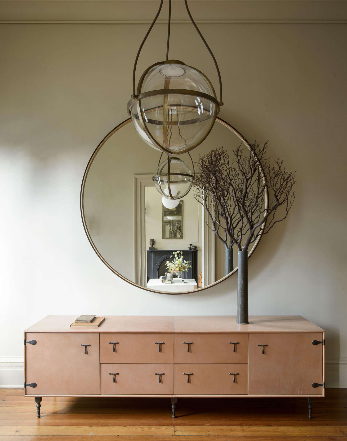 TheLeather Mid Credenza and theLeather Round Mirror are from BDDW in NYC. The hallway is illuminated by a Kensington Pendant in hewn brass, designed by Michael Amato for Urban Electric Co.