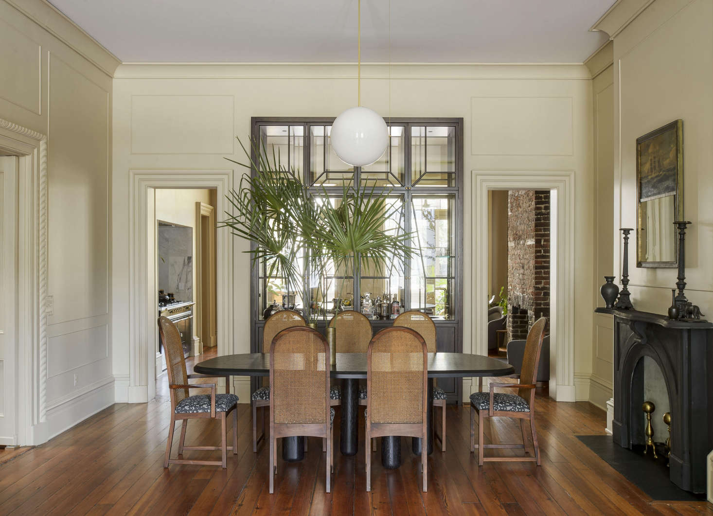 In the dining room, a custom built-inglass vitrine, modeled after an English breakfront cabinet, affords a view into the kitchen. A Workstead Signal Globe Pendant hovers over the dining table.